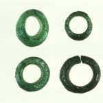 four circular green glass beads