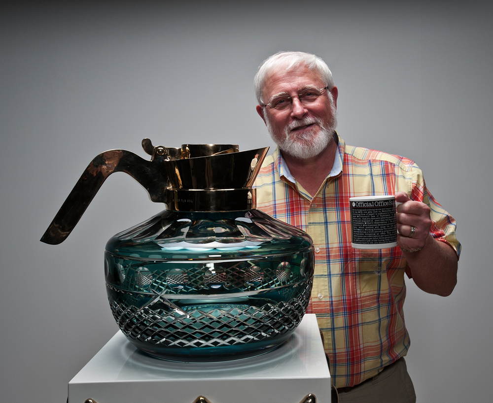 Museum photographer Nick Williams holds up a coffee mug next to the object