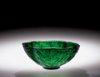 Islamic bowl on loan to a traveling exhibition that will be on display in Provo, UT, Indianapolis, Houston, and Brooklyn. Bowl, transparent emerald-green, mold-pressed and cut. Islamic; Western Asia; perhaps Iran, c. 9-10th century. H: 7.6 cm.(55.1.136)