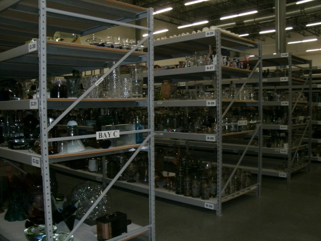 Shelves full of glass in The Corning Museum of Glass' warehouse.