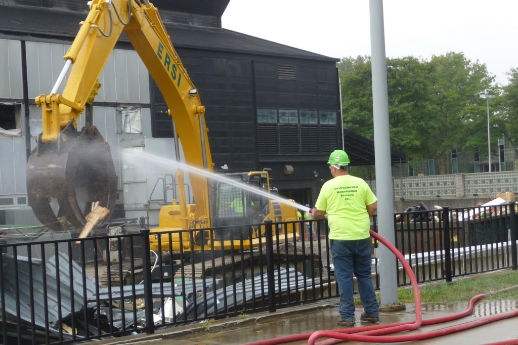 Spraying the debris with water to control dust
