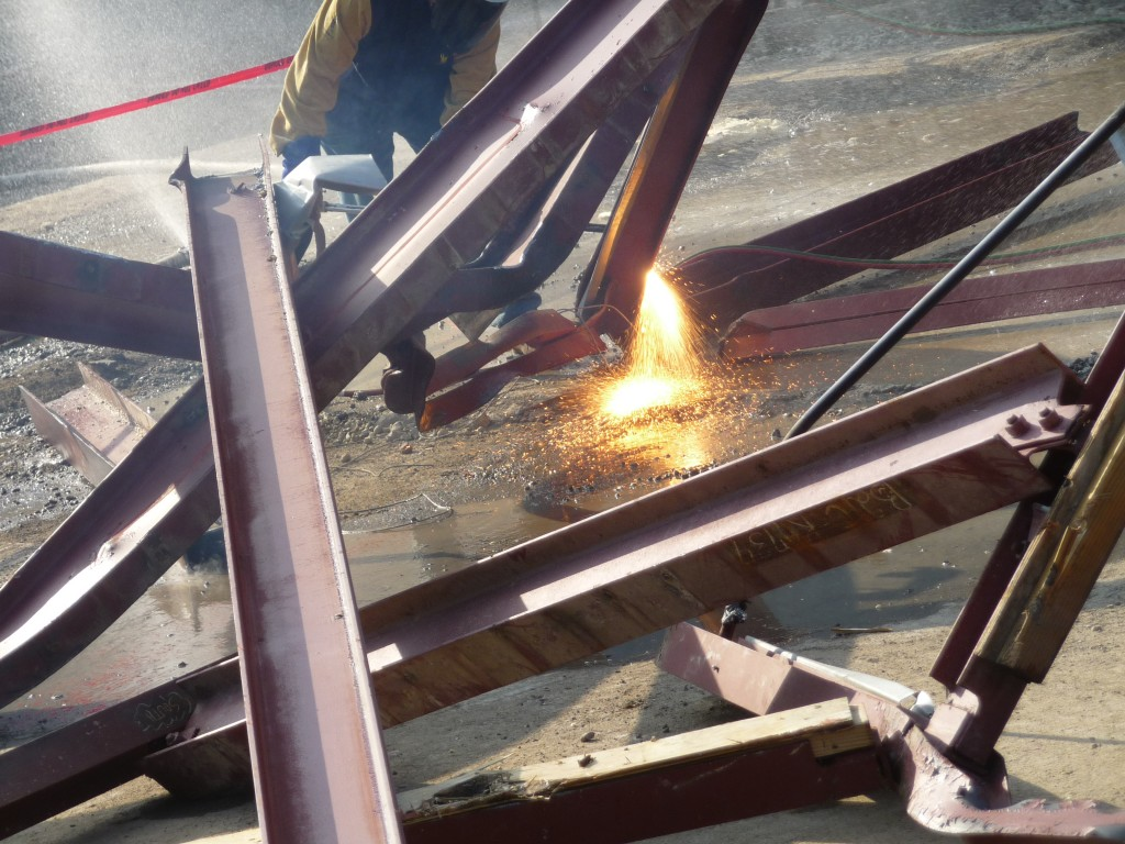 Steel beams are cut with oxy-propane torches for transport