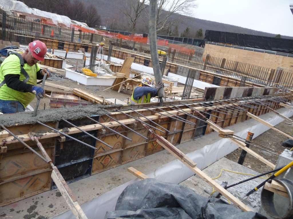 Concrete is pumped into the wall form