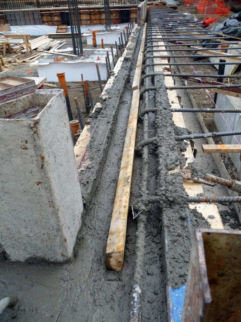 Wood is pushed into the top of the cement to create keyways to lock in the next pour.