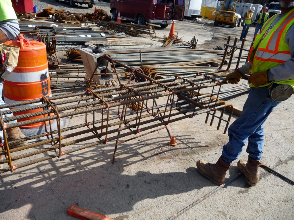 Workers assemble the column rebar using tie wire
