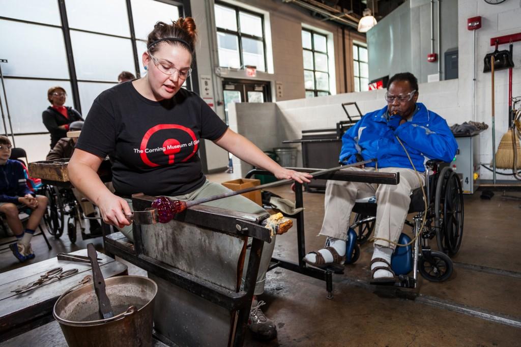 Glassmaker Christa Westbrook assists a Veteran in making a glass pumpkin.