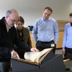 Galbraith and staff members examine a rare book.