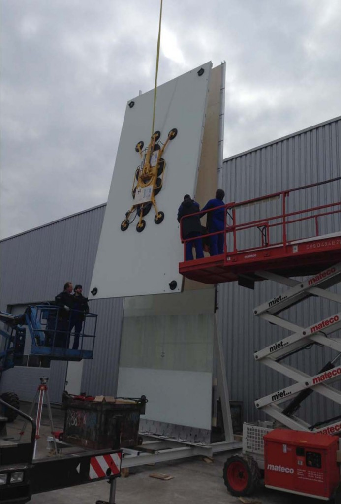 The upper panel is hoisted into position.