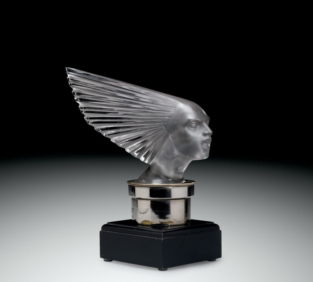Automobile Mascot, Victoire (Victory), mold-pressed glass, acid-etched; metal radiator cap, wood base.  René Lalique (French, 1860–1945).  France, Combs-la-Ville or Wingen-sur-Moder, Lalique et Cie., designed 1928.  H. 23 cm, W. 24.6 cm, D. 10.1 cm.  The Corning Museum of Glass (2011.3.345, gift of Elaine and Stanford Steppa)