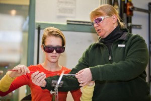 Glady West assisting flameworking at the Holiday Open House.
