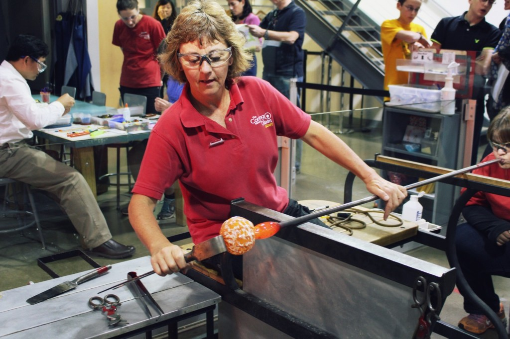 At the Make Your Own Glass hot shop, Jackie helps a guest blow a glass ornament.