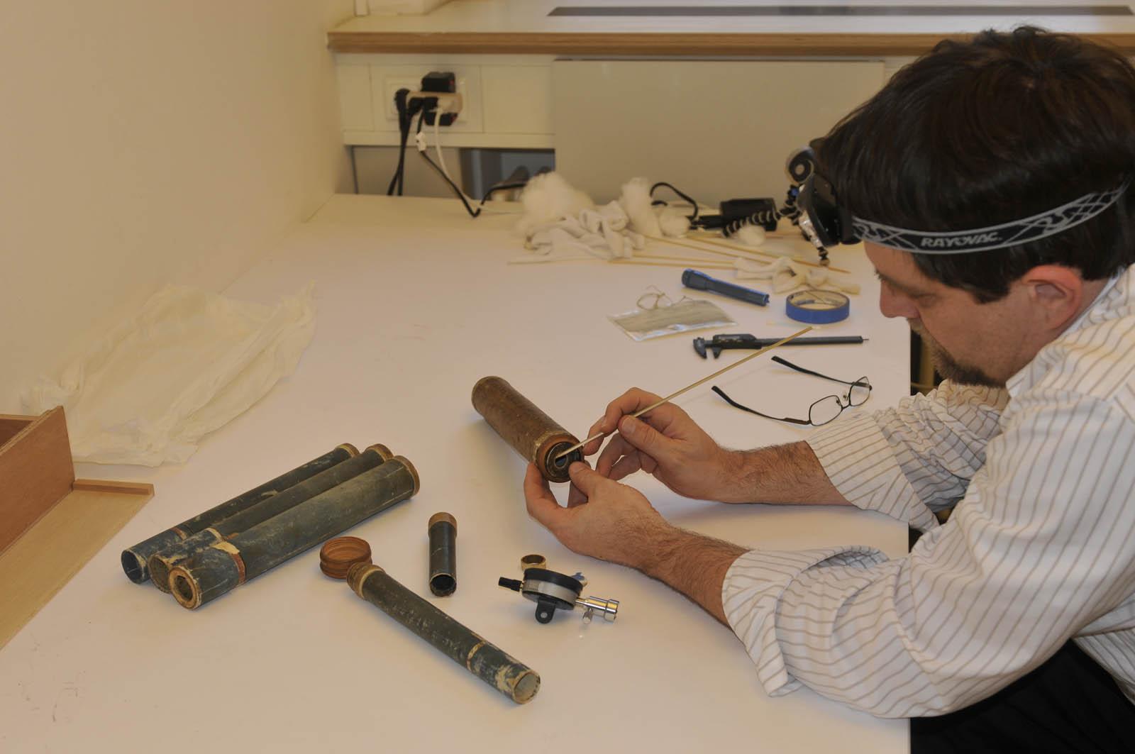 Dr. Bolt examines an early telescope.
