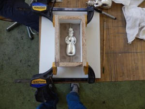 Half of the mold box is filled with clay, and the ornament is depressed halfway into the clay.