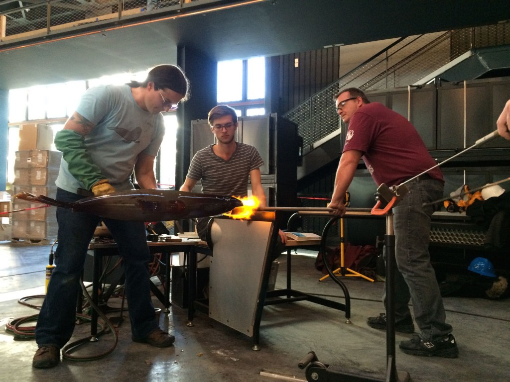 Raven Skyriver works with his team to create a sculpted glass seal.