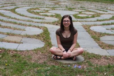 Liz Caroscio sits next to her buried glass planet.