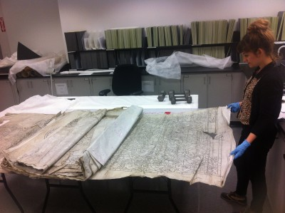 Nicole unrolls a roll of waxed canvas tracings.