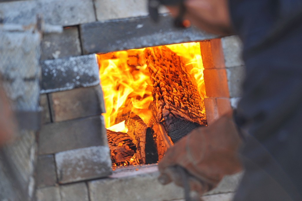 Professor Fred Herbst stokes wood into the firebox of one of Corning Community College's wood-fired kilns. These well-drafted kilns can achieve temperatures in excess of 2200°F.