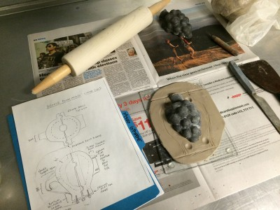 A diagram of the desired exterior shape, along with the set up before wax is applied to the silicone grape cluster.