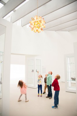 Kids in the gallery looking up at Sphere Chandelier from the Candy Collection