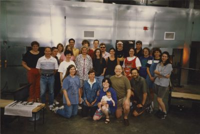 Amy, Bill, and their young daughter pose for a group picture with an early class at The Studio.