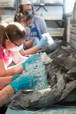 Students are seen removing the plaster cast to get a look at their near completed works.