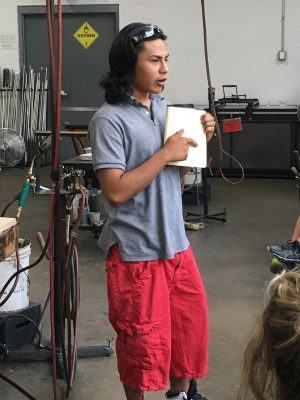 Roberto explains his concept sketches to his classmates.