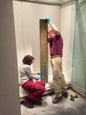 A sample column on loan from the Chrysler Museum of Art is carefully installed in its display.
