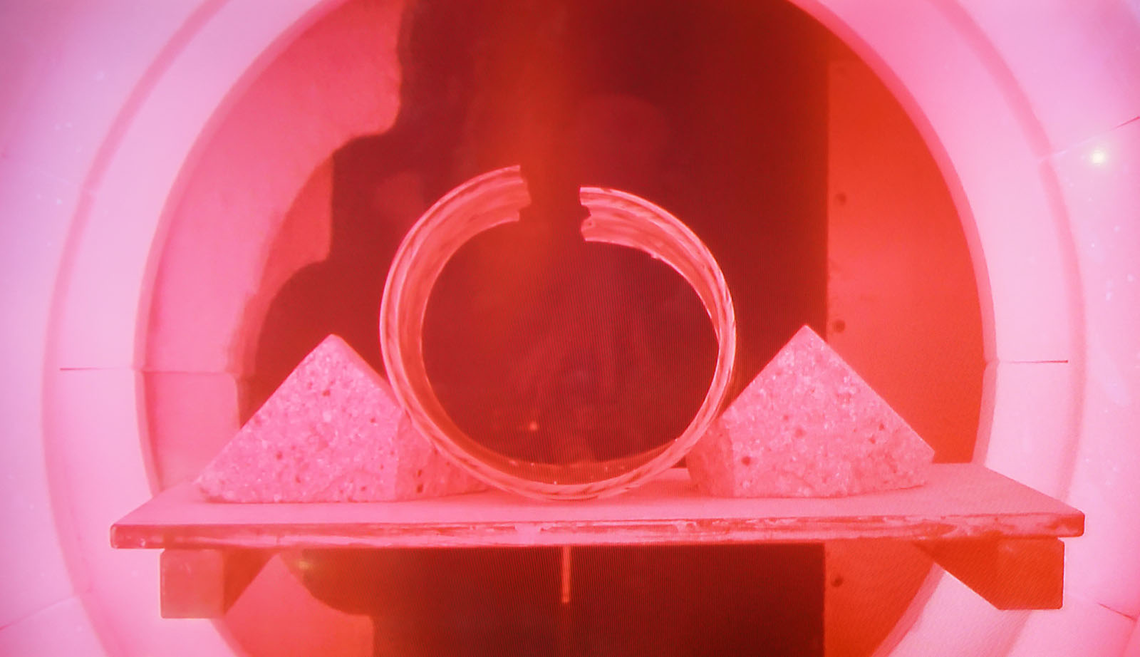 The split cylinder begins to soften in the heated chamber.