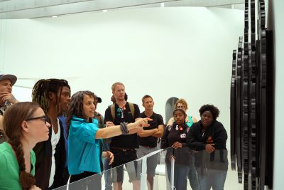 Susie Silbert (fourth from left), curator of modern and contemporary glass, leads the Expanding Horizons students and mentors on a tour of the Contemporary Art + Design Galleries.