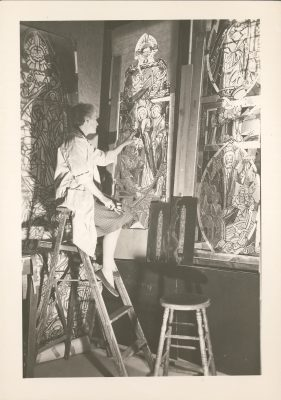 A photo from the collection showing Katharine Lamb Tait working on a stained glass window during her time as Head Designer at J & R Lamb Studios, her family's firm. The cartoon is displayed on the wall behind her and there are two matted window designs to help guide her work.