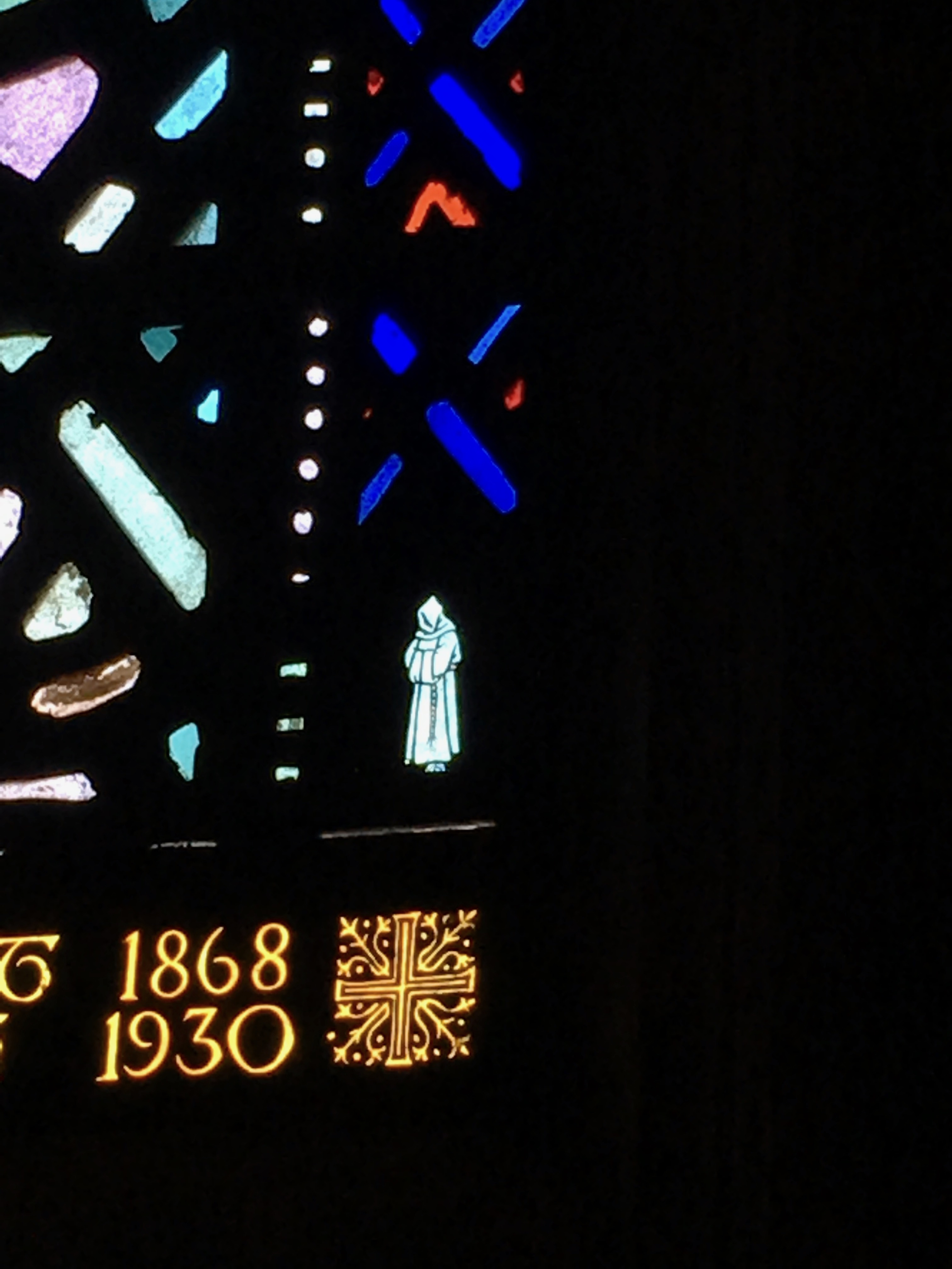 A white friar in the bottom of one of the windows from the Church of the Heavenly Rest.