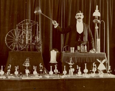 A glassworker, possibly F.A. Owen, and his steam-powered glass engine.