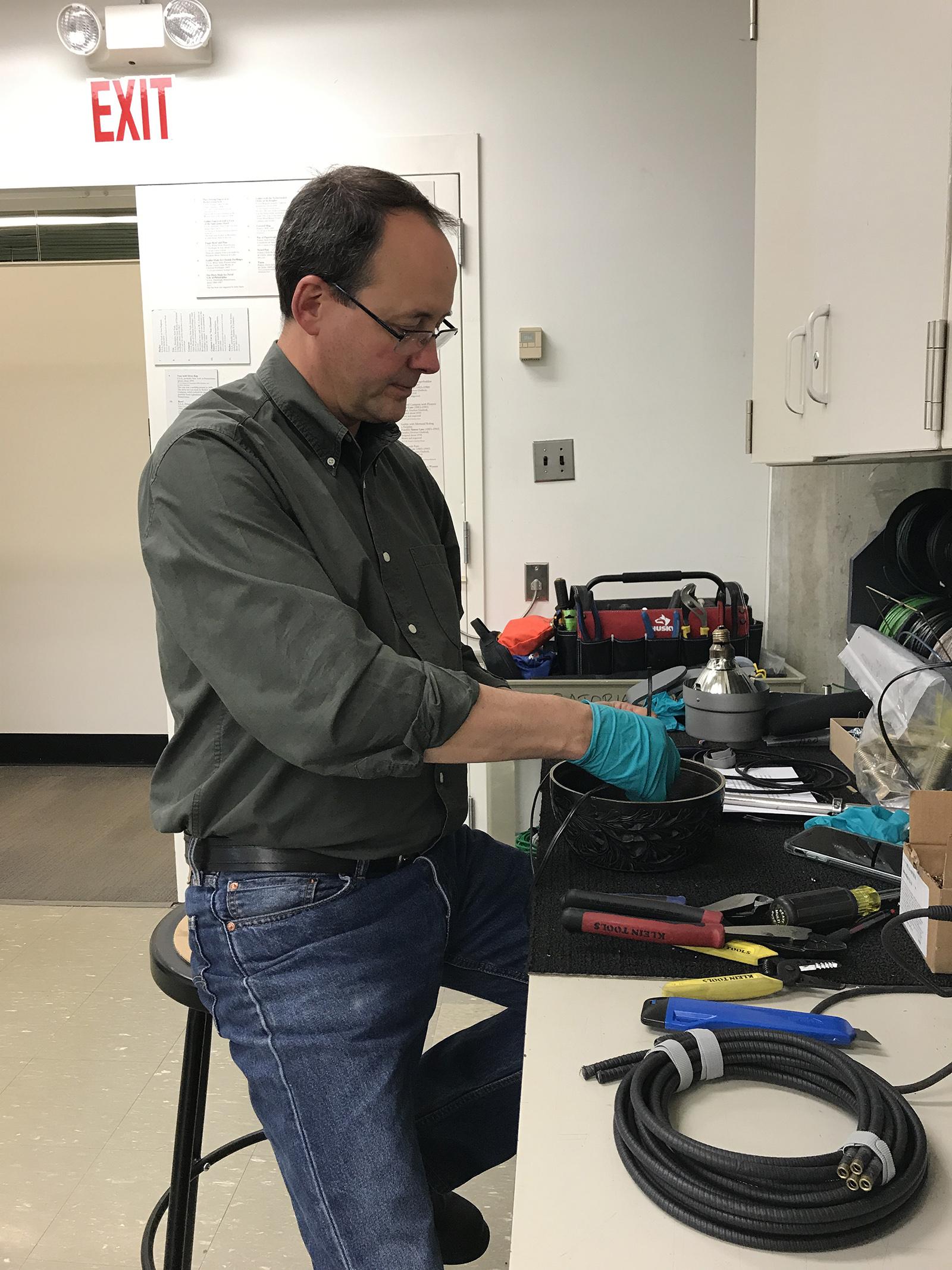 Dave Kuentz, Preparator, rewiring and replacing bulbs.