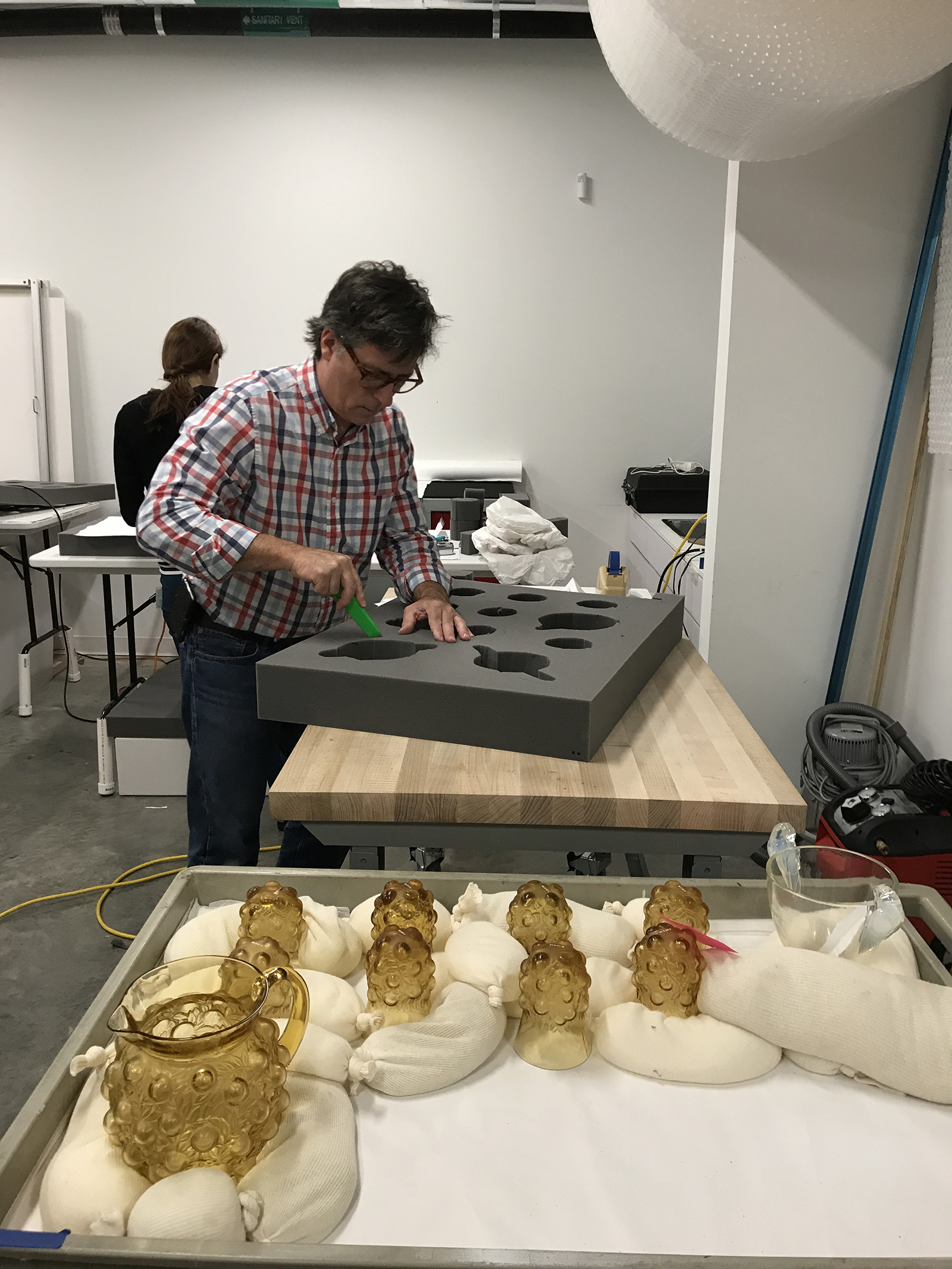 Tom cuts a void into the foam to fit each object.