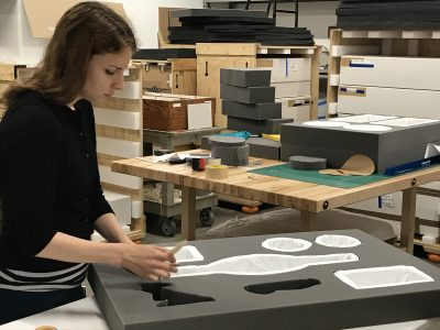 Noelle Ward, Collections Intern, pads each cutout with a soft material for protection.