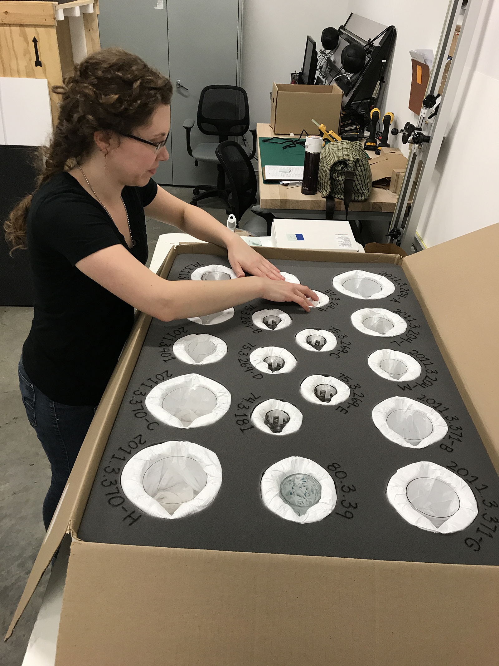 Lindsay Nikisher, Preparator, makes sure all objects fit snugly in their correct place.