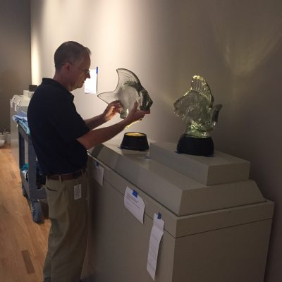 Steve carefully positioning the lamps in the open display case.