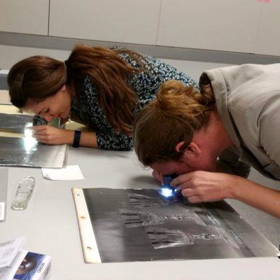 Ilaria and Erin examine silver gelatin photographs.