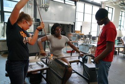 Teamwork is key when it comes to glassmaking. Nikki assists student Ja Mia Johnson as Trevelli Jones looks on.