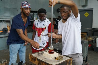 Jalen Pittman assists N'Kosi Barber (mentor) with a glass heart as Julian watches.