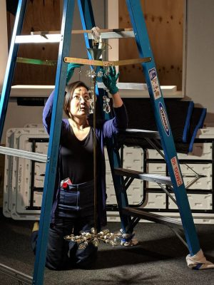 Assistant conservator Lianne Uesato conditions the Loebmeyr chandelier.