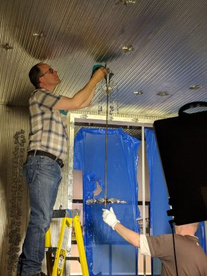 Preparator and resident electrician Dave Kuentz and MAK's Harald Bauer complete installation of the chandelier.