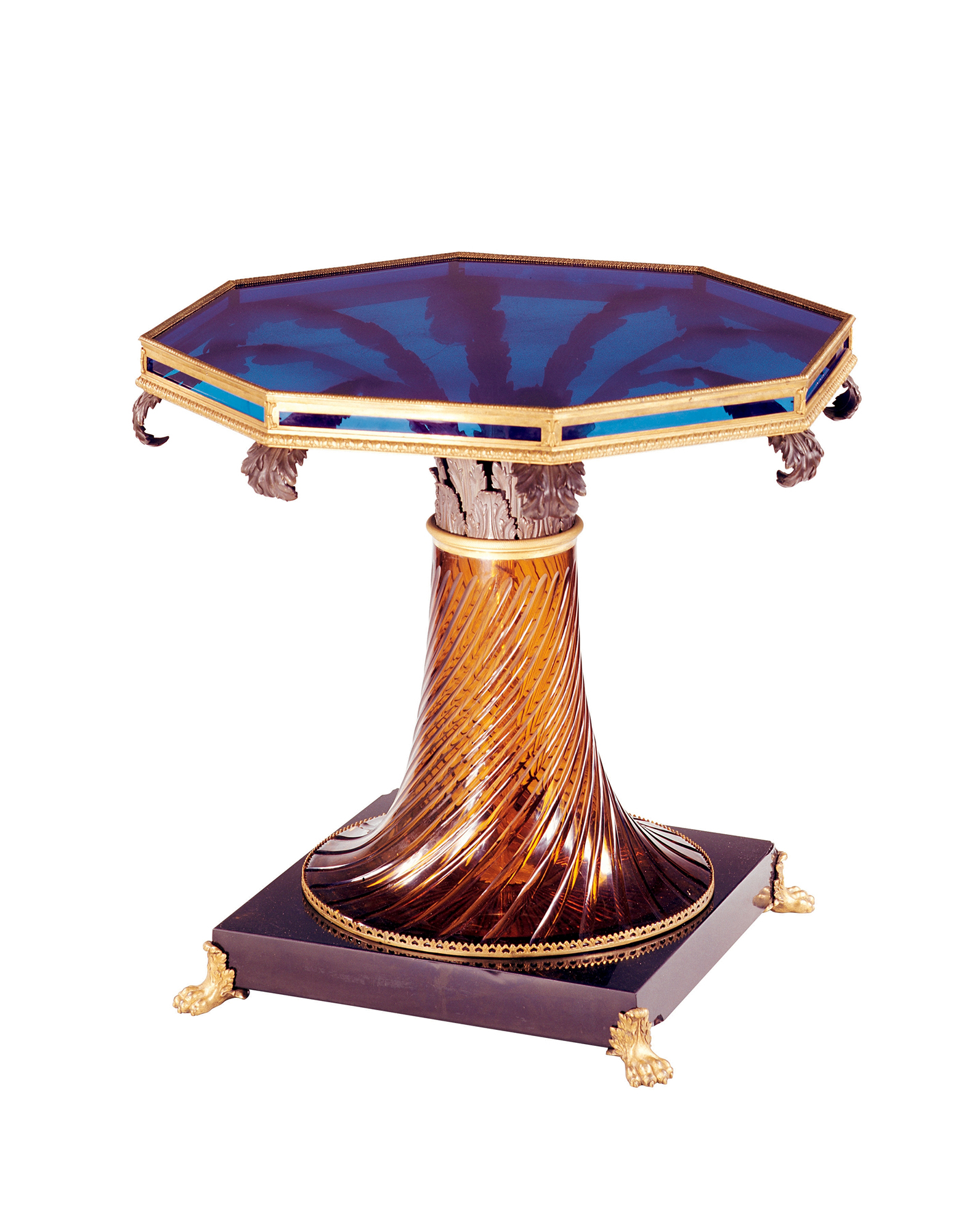 The table top is a single slab of blue glass cut in the shape of an octagon, resting on a single piece of amber-colored glass decorated with spiral cuttings.