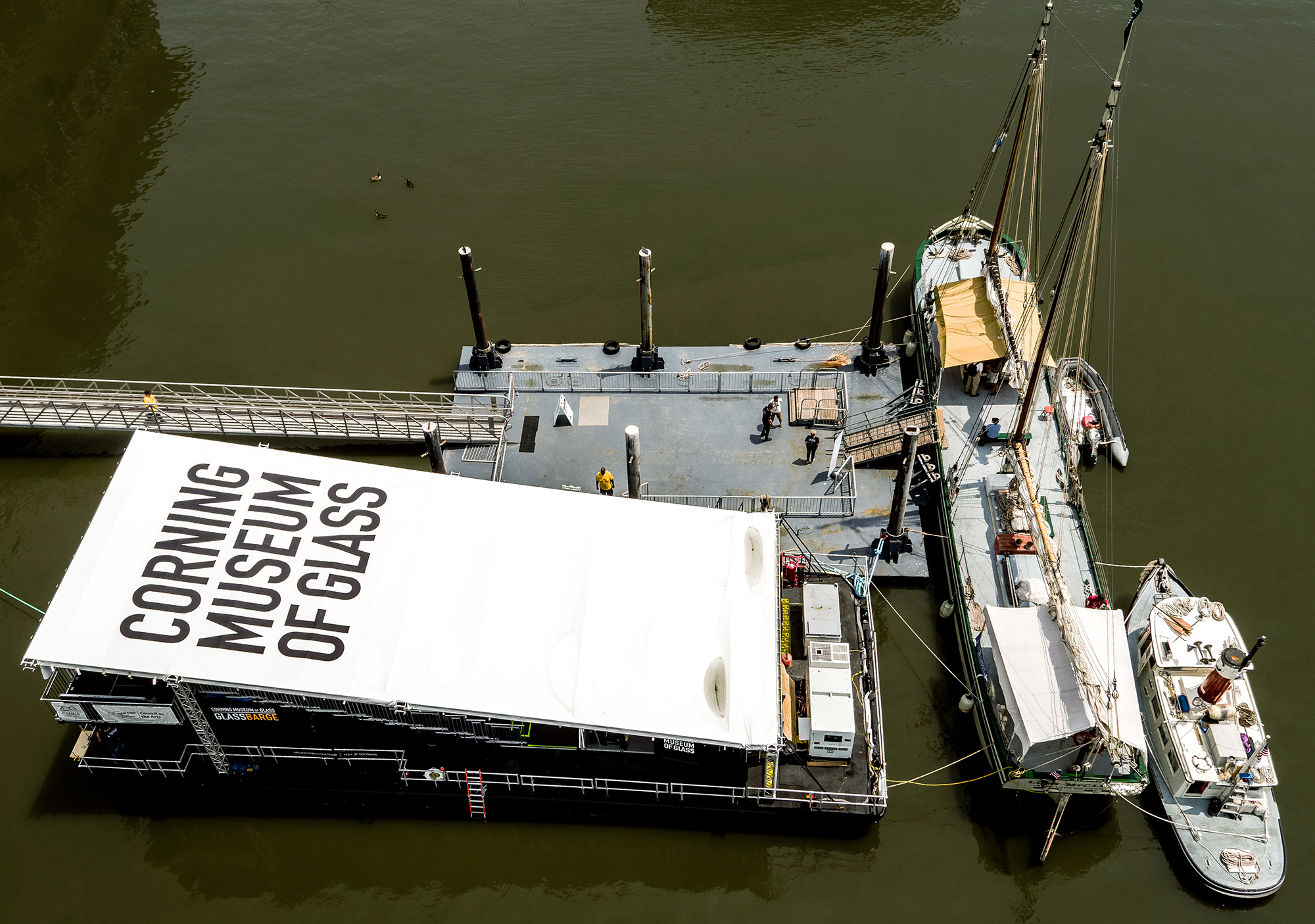 Aerial view of GlassBarge, the Lois McClure, and the C.L. Churchill docked on the Hudson River.