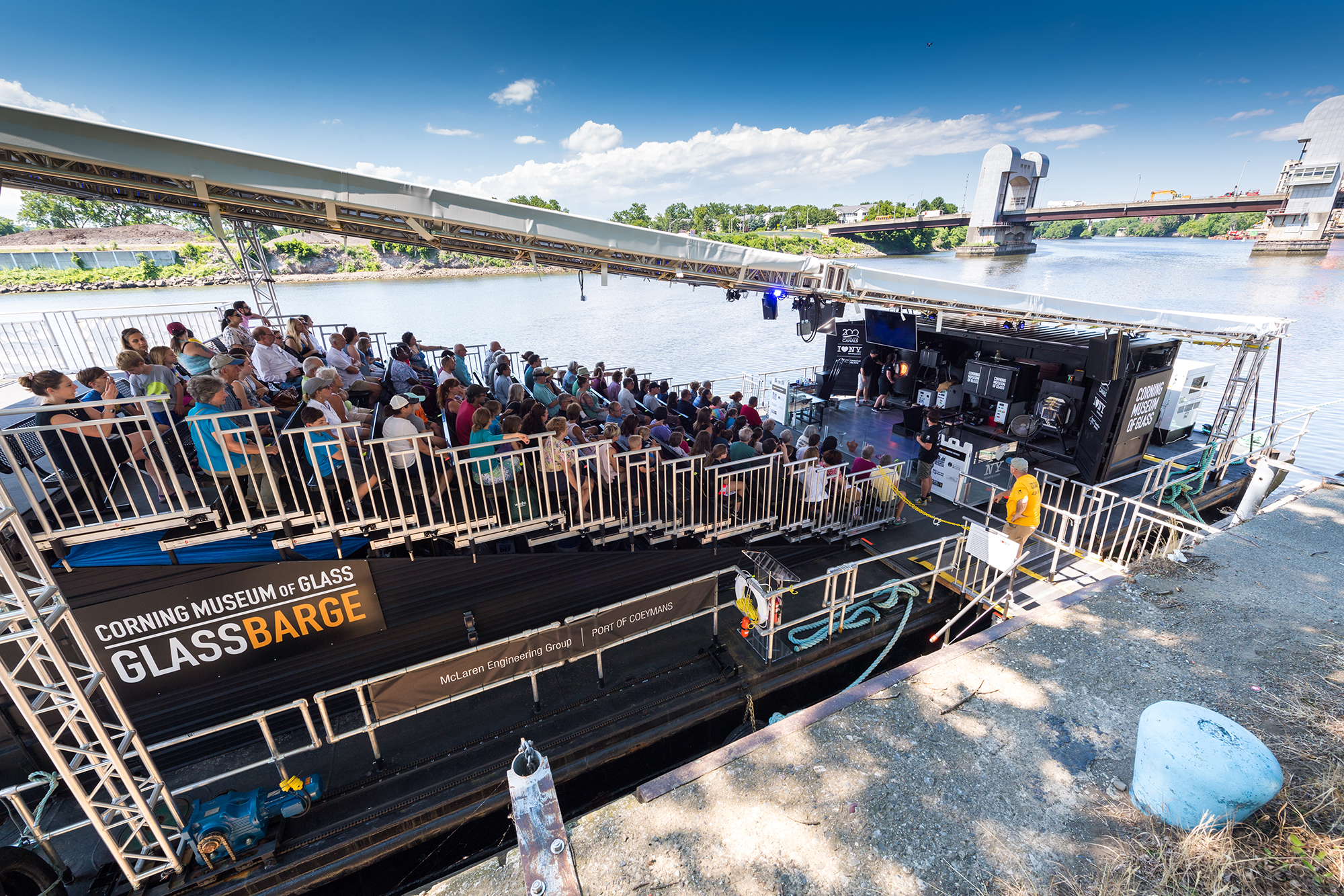 Barge with stadium seating docked on the Hudson River with visitors watching glassblowing.
