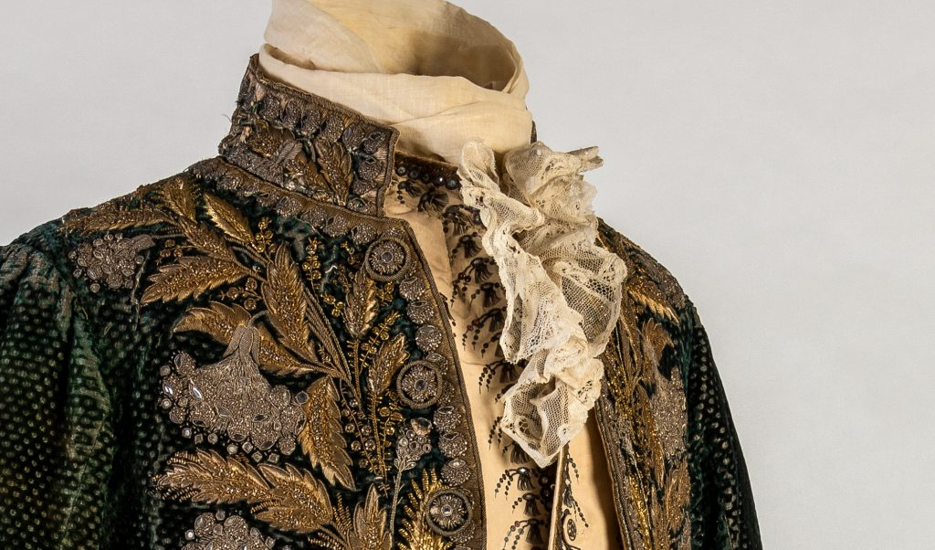 a finely embroidered period jacket pictured on a mannequin from the chest up to the neck, with a ruffled shirt appearing between the lapels. The jacket looks blue with gold and silver decorations.