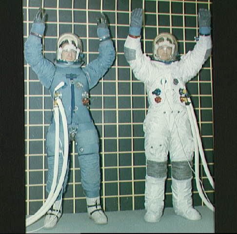 Comparison of the original design of Block II Apollo spacesuits. On the left astronaut James B. Irwin wears the pre-fire design, while John Bull (right) wears the revised suit featuring a beta cloth outer layer. Courtesy NASA on the Commons
