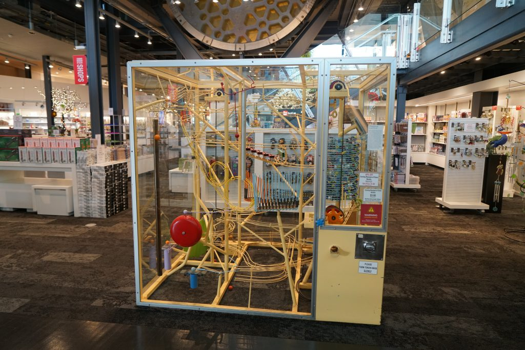 A 6 foot tall kinetic marble machine stands in the middle of the Museum shops. It has multiple tracks and obstacles that marbles roll along, interacting with instruments to make noises as they go.
