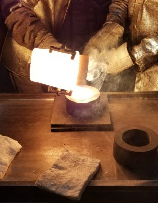 One man pours molten glass into a small mold being held in place by another man.