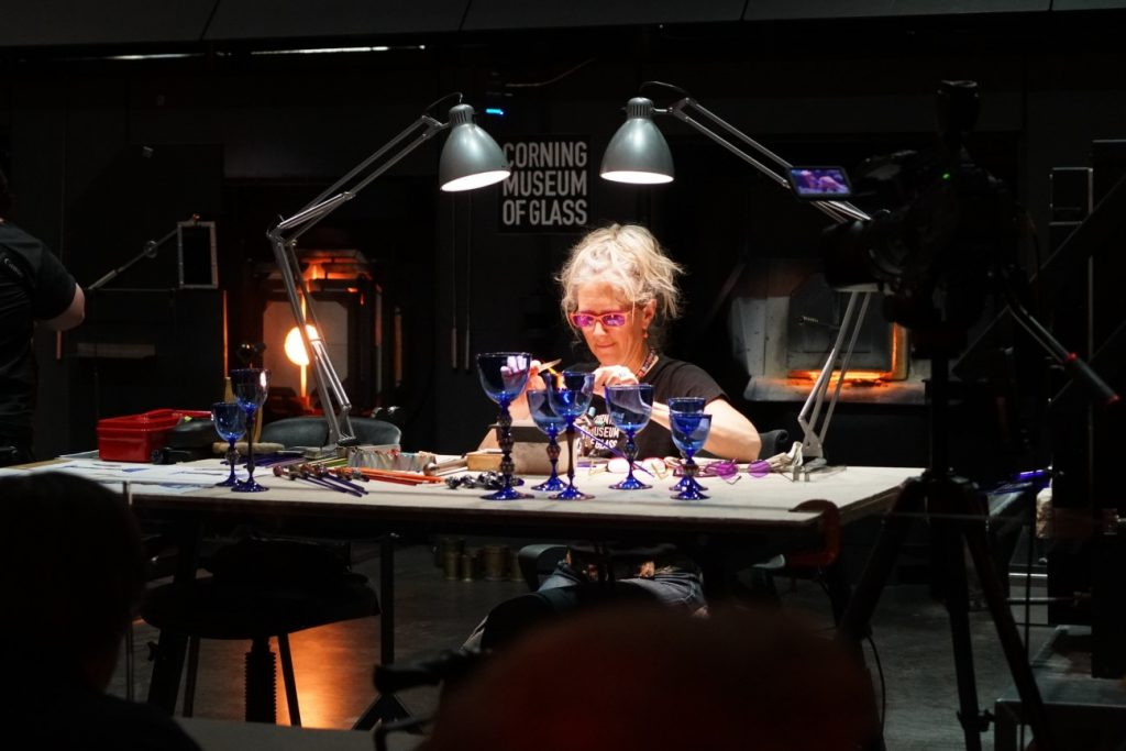 Artist Kristina Logan sits at a table turning a small piece of glass over a flameworkers torch.